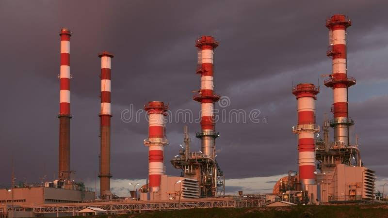 Parte de uma refinaria de petróleo e de um central energética no crepúsculo imagens de stock