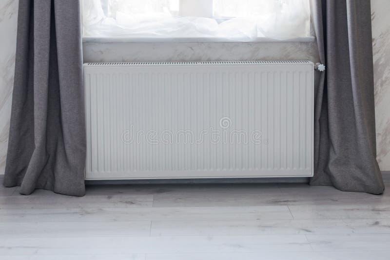 Parte de uma sala brilhante com o radiador do engodo do aquecimento instalado sob a janela imagem de stock royalty free