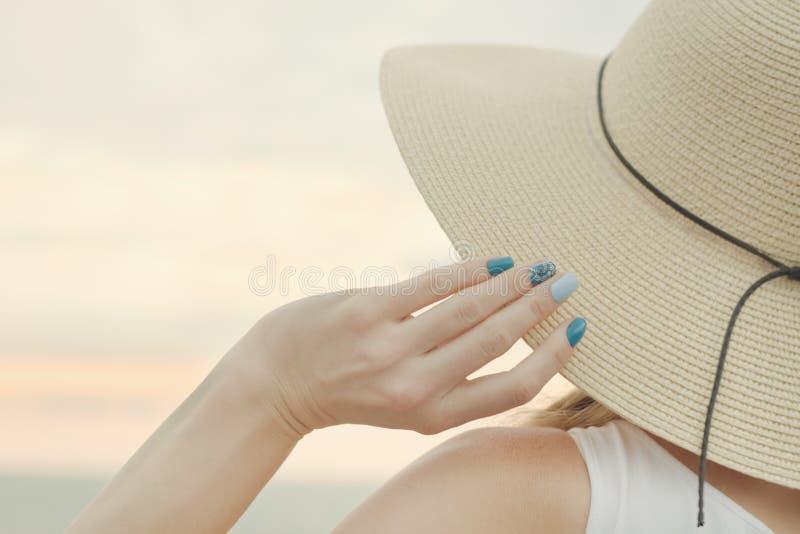 Parte de un sombrero y de un cierre femenino de la mano para arriba Cielo de la puesta del sol en la parte posterior foto de archivo