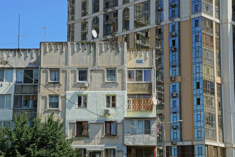 Parte de una casa gris vieja con los balcones y las ventanas delante de un nuevo edificio grande imagenes de archivo