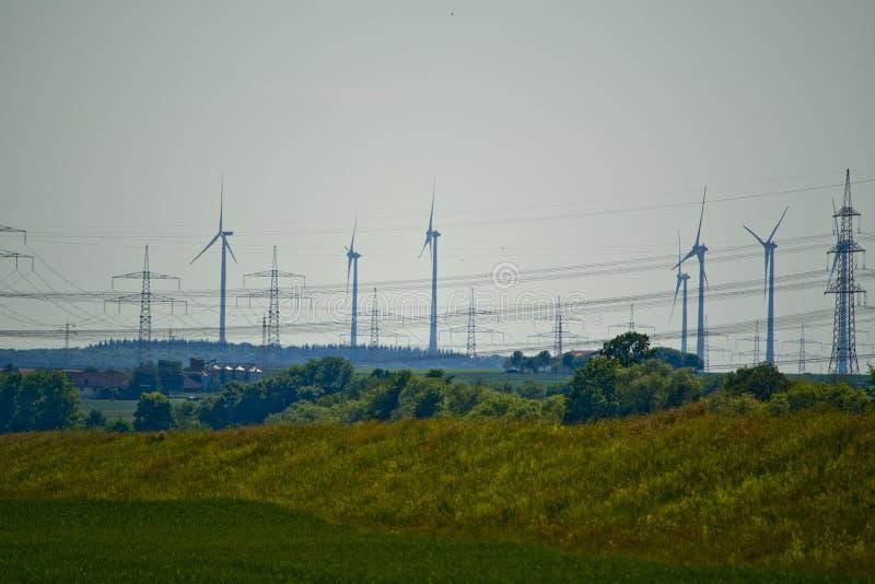 Parte de una línea eléctrica con las turbinas de viento en Baviera, Alemania foto de archivo