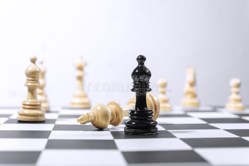 Parte de xadrez de madeira do rei derrotada pela parte de xadrez preta do bispo fotos de stock royalty free