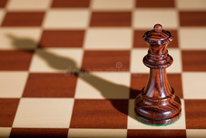 Parte de xadrez - uma rainha preta em um tabuleiro de xadrez. imagem de stock