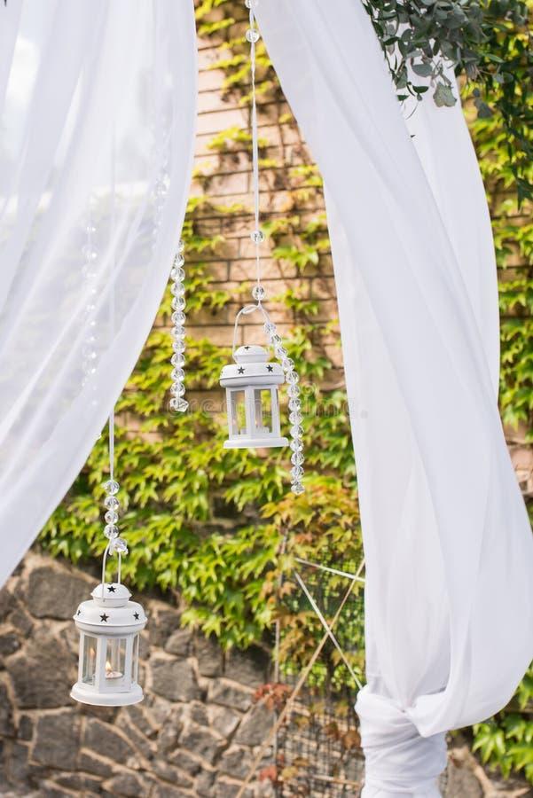 Parte del arco de la boda adornada con la linterna blanca con una vela y un manojo hermoso de eucalipto fotos de archivo libres de regalías