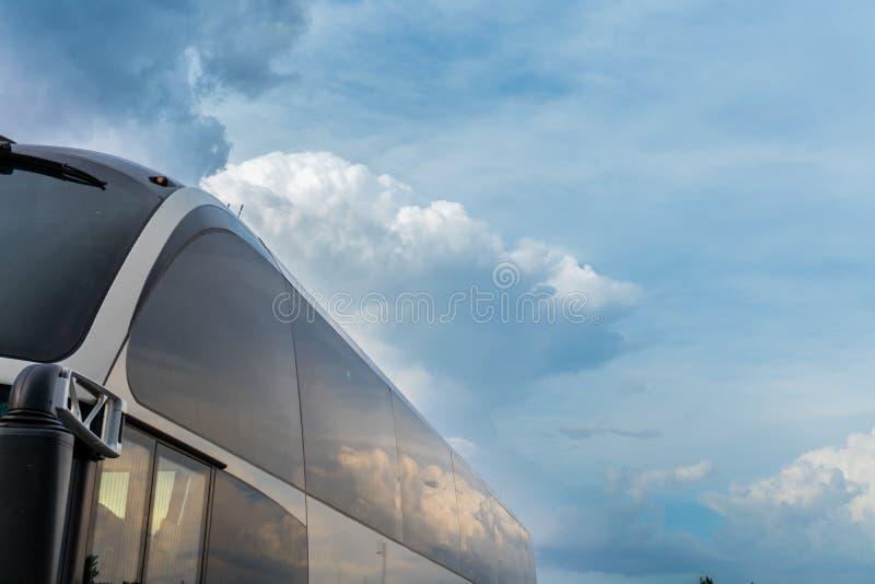 Parte del bus turistico con le nuvole delicatamente blu o bianche per la vostra disposizione o manifesto di pubblicità fotografia stock