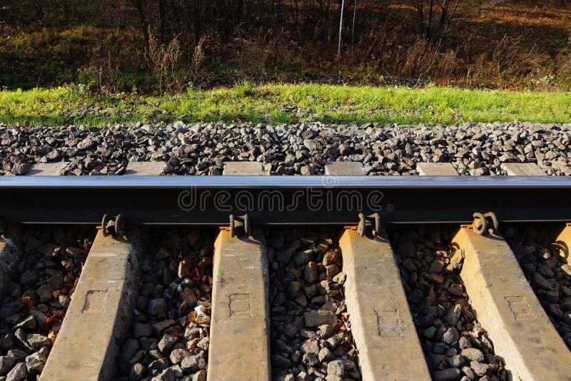 Parte del ferrocarril con un carril del hierro y de durmientes concretos en pequeños escombros grises e hierba verde en el lado d imagenes de archivo