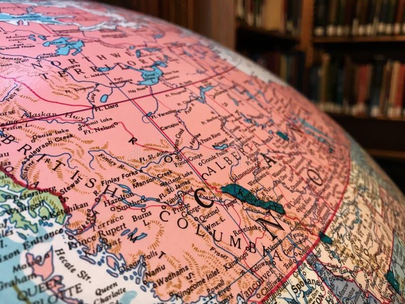 Parte del globo de la tierra con un mapa pol?tico en el fondo de libros fotos de archivo libres de regalías