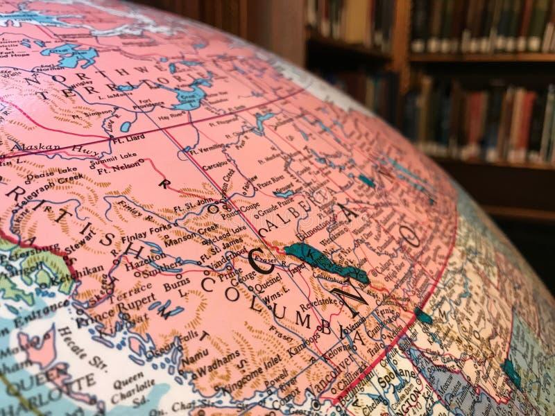 Parte del globo de la tierra con un mapa pol?tico en el fondo de libros foto de archivo