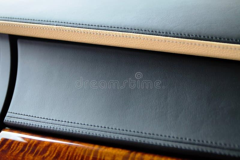 Parte del interior del coche de lujo costoso El panel auténtico de la caja de guantes de cuero en color negro y beige cosido y ba fotografía de archivo