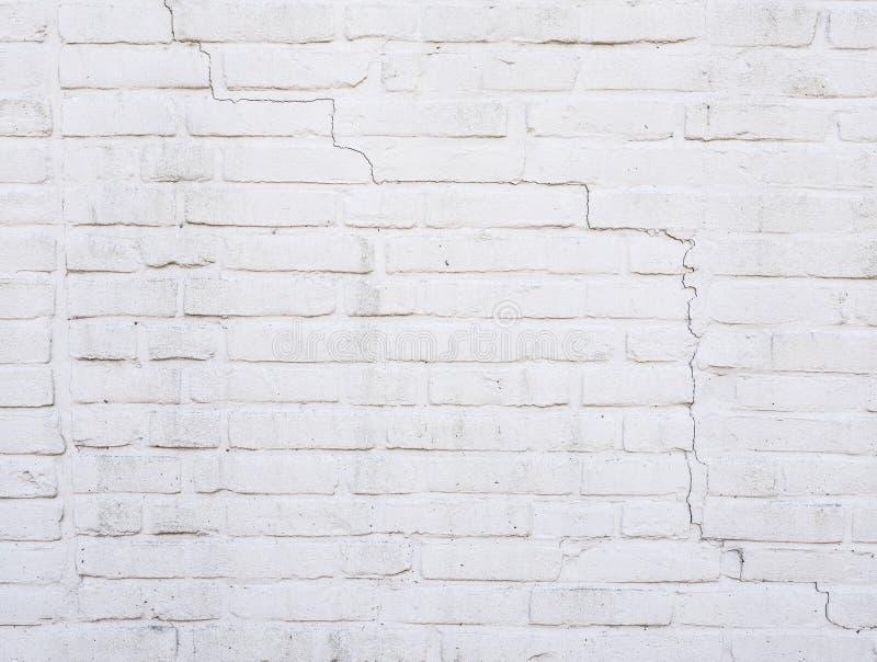 Parte del muro di mattoni dipinto bianco con la crepa immagini stock