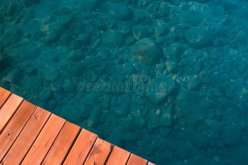 Parte del pilastro di legno e di chiara acqua di mare dell'acqua, pietre visibili immagine stock