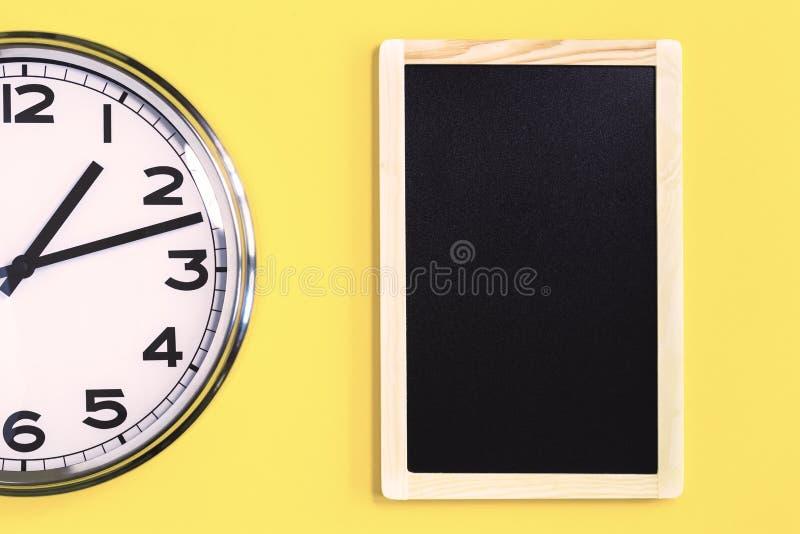 Parte del reloj de pared y del tablón de anuncios negro en fondo amarillo foto de archivo