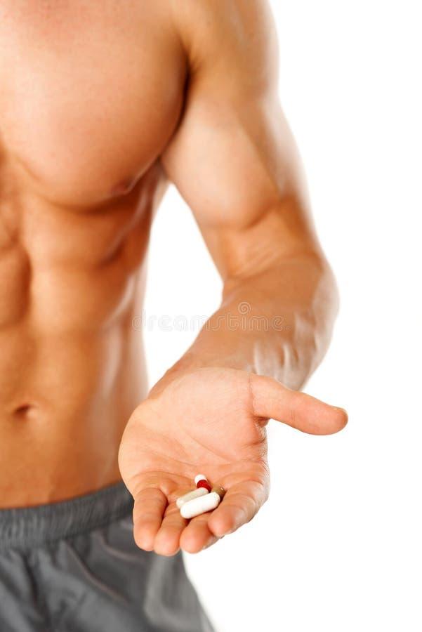 Parte del torso muscolare dell'uomo con la mano piena delle pillole immagini stock