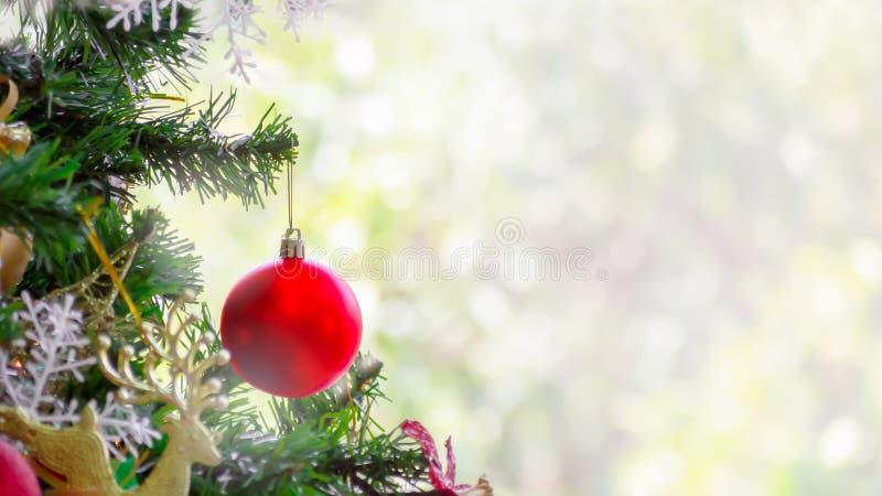 Parte dell'albero di Natale con la palla rossa di natale sul fondo verde e bianco del bokeh immagine stock