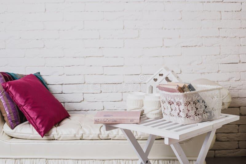Parte dell'interno con lo strato ed i cuscini decorativi, tavola di legno bianca con i libri su  immagini stock