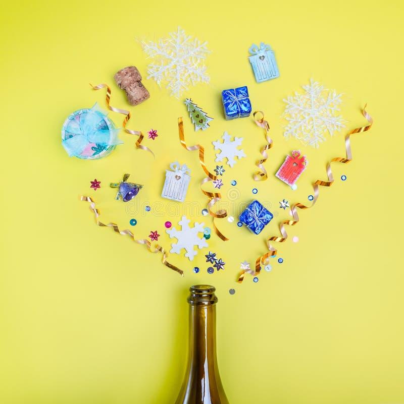 Parte della bottiglia del partito del champagne con i coriandoli dei regali, zecchini, nastri, fiocchi di neve su fondo giallo lu fotografie stock libere da diritti