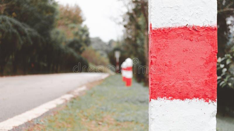 Parte della pietra miliare con la strada vaga come fondo, speranza per successo immagini stock