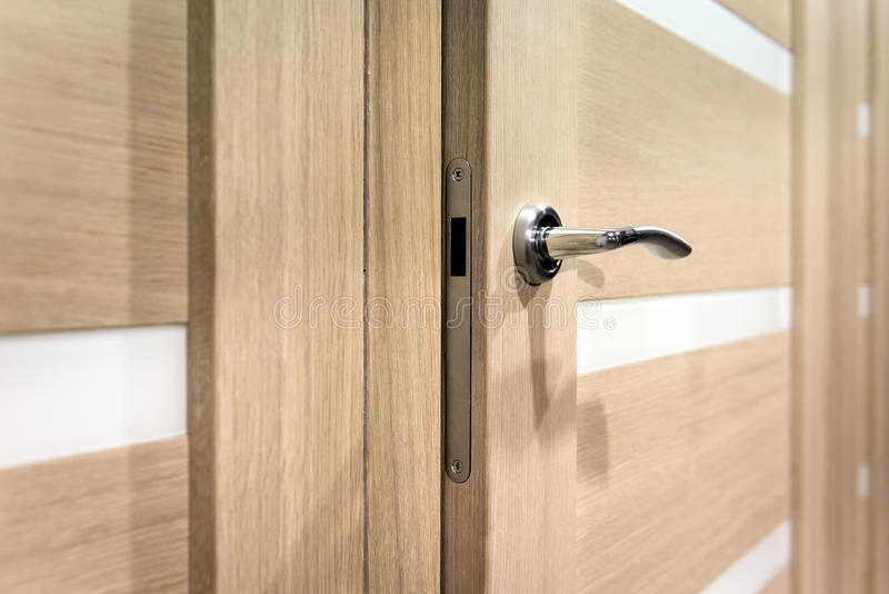 Parte della porta aperta con la maniglia della porta d'argento fotografia stock libera da diritti