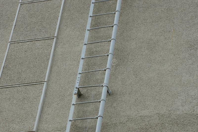 Parte della scala del ghisa grigio sul muro di cemento della costruzione fotografie stock libere da diritti