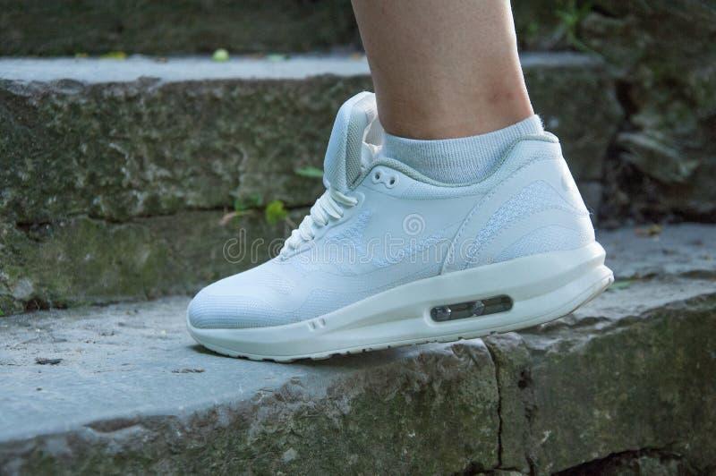 Parte delle gambe di una donna in scarpe da tennis bianche che cammina lungo i punti di pietra fotografie stock libere da diritti