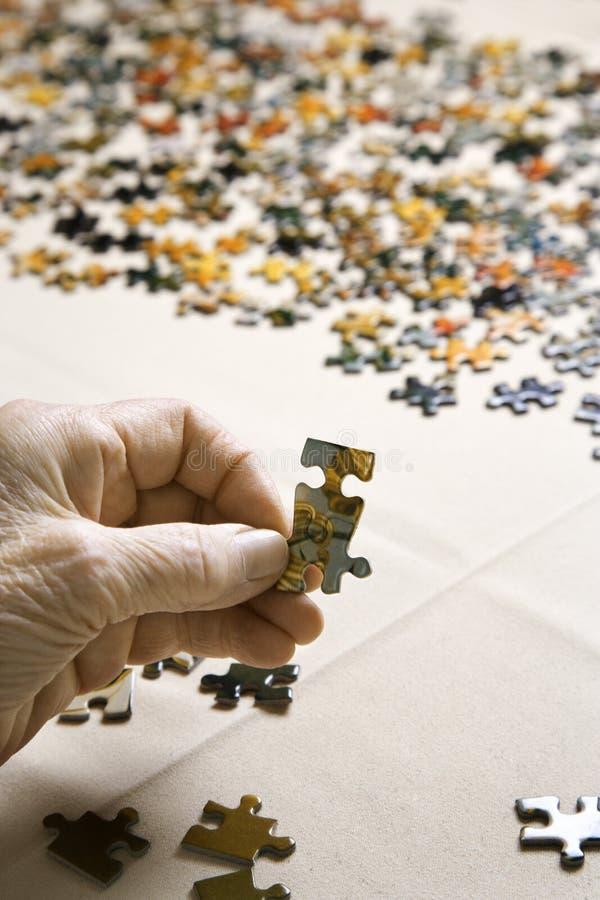 Parte di puzzle della holding della mano. fotografie stock libere da diritti