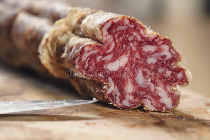 Parte di salame italiano secco sulla tavola immagine stock