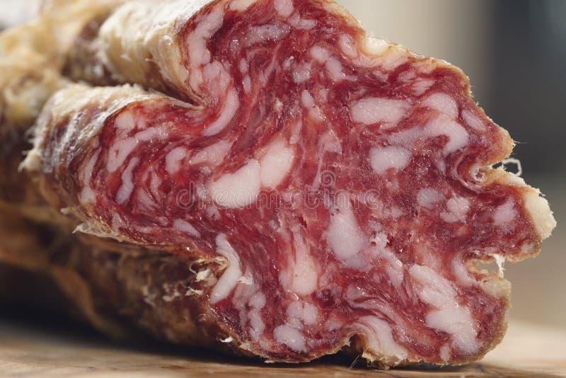 Parte di salame italiano secco sulla tavola fotografia stock libera da diritti