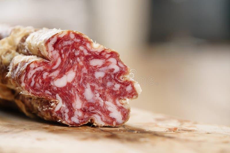 Parte di salame italiano secco sulla tavola fotografie stock