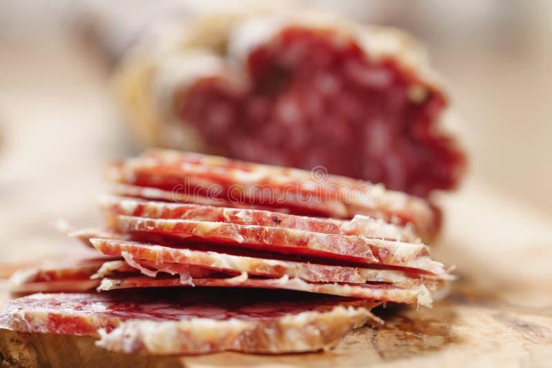 Parte di salame italiano secco sulla tavola immagini stock libere da diritti