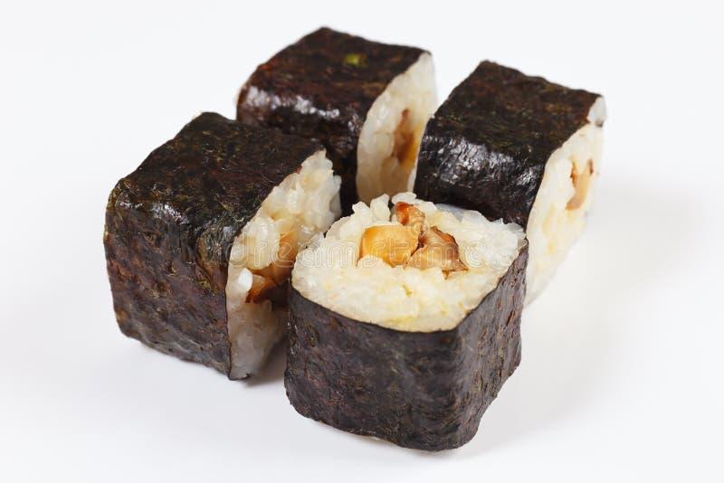 Parte di sushi con il unagi e di funghi su un primo piano bianco del fondo immagini stock