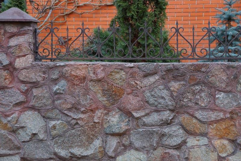 Parte di un recinto di pietra marrone con i tondini di ferro taglienti immagine stock