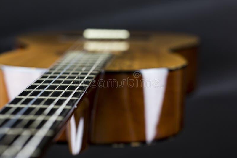 Parte di una chitarra acustica arancio sul sorso nero FOD del colpo del primo piano del fondo immagine stock