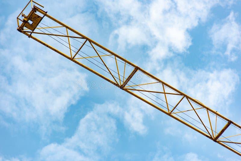 Parte di una gru di costruzione gialla contro un cielo blu fotografie stock