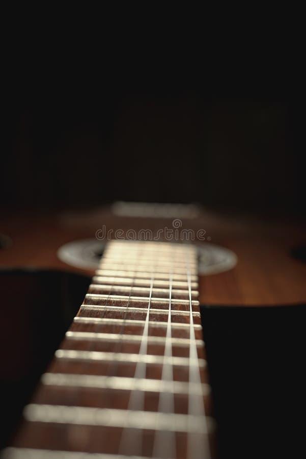 Parte di vecchia chitarra marrone con le corde su un fondo di legno scuro fotografia stock