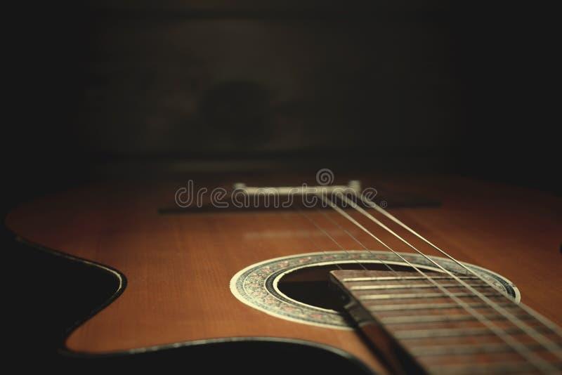 Parte di vecchia chitarra marrone con le corde su un fondo di legno scuro fotografie stock