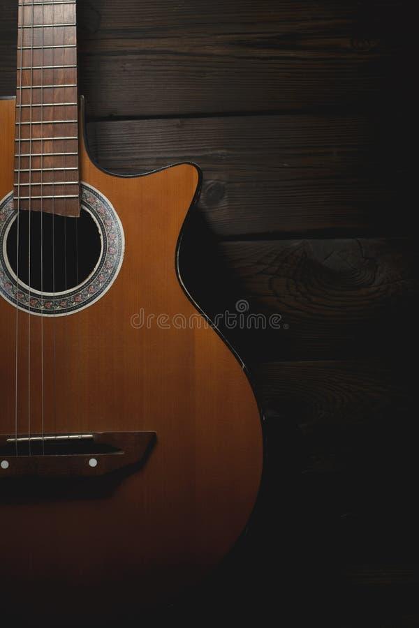Parte di vecchia chitarra marrone con le corde su un fondo di legno scuro immagini stock