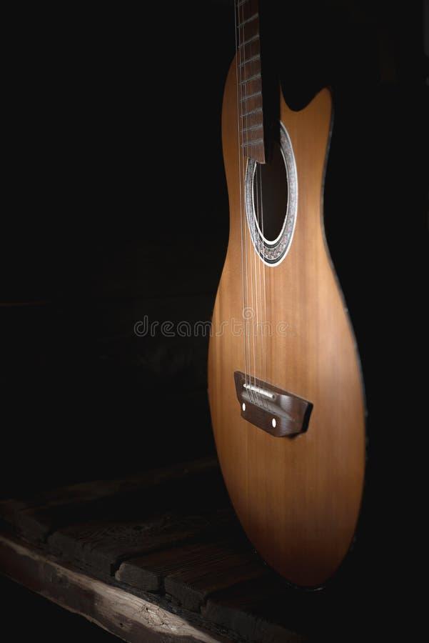 Parte di vecchia chitarra marrone con le corde su un fondo di legno scuro immagine stock libera da diritti