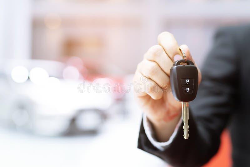 Parte dianteira da chave do carro da terra arrendada da mão do homem de negócio com o carro na sala de exposições fotografia de stock royalty free