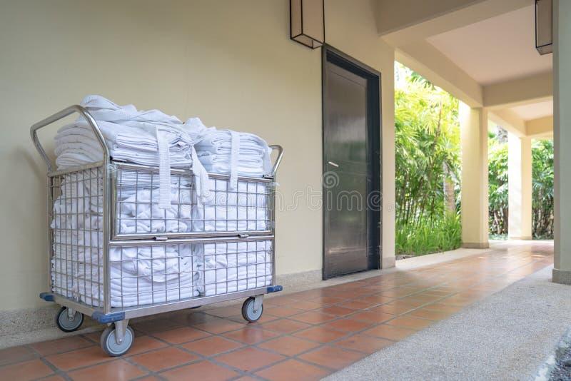 Parte dianteira de estacionamento do trole da empregada doméstica do hotel da sala com toalha limpa e roupões prontos para mudar  fotografia de stock royalty free