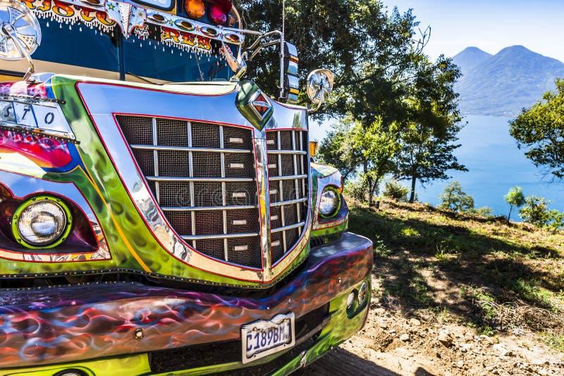 Parte dianteira do ônibus público & vista do lago Atitlan & dos vulcões, Guatemala fotos de stock