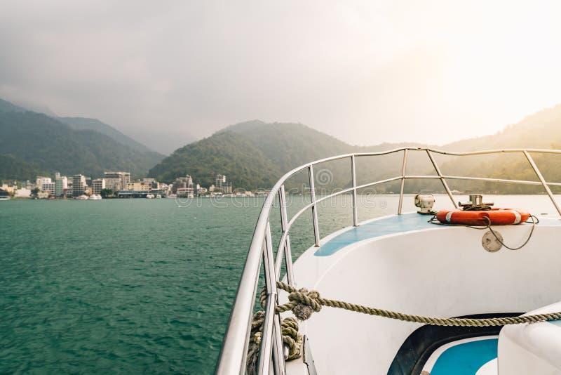 Parte dianteira do barco do curso com boia salva-vidas e da luz dourada sobre o lago moon de Sun com montanha e a cidade no fundo foto de stock royalty free