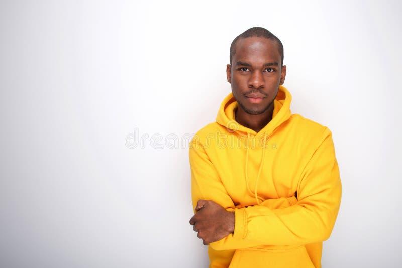 Parte dianteira do homem afro-americano fresco no hoodie contra a parede branca fotografia de stock