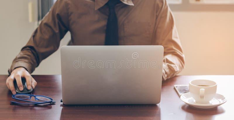 Parte dianteira do homem de negócios que usa o portátil que trabalha no escritório com telefone celular e café imagens de stock