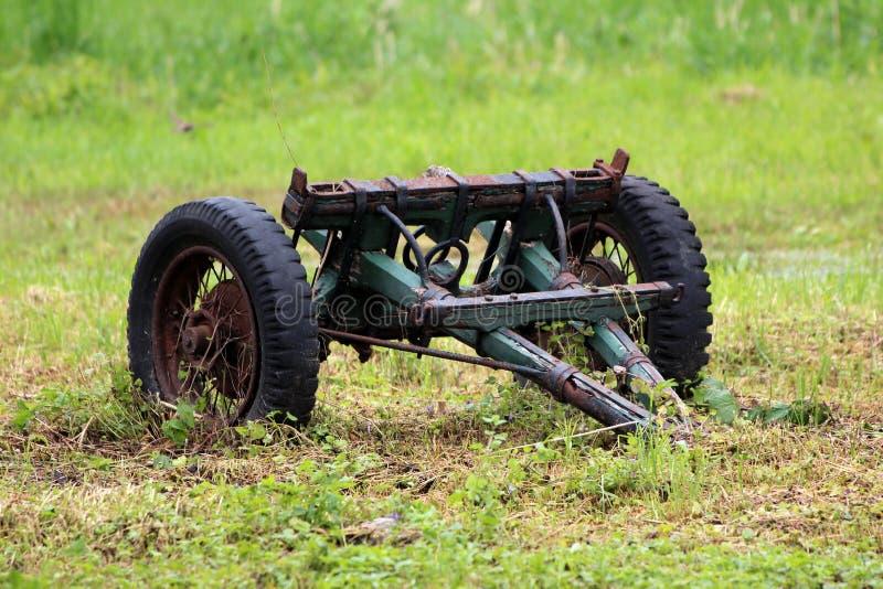 Parte dianteira do reboque de trator noun caseiro retro do vintage de madeira com pesadamente - os pneus usados e o quadro oxidad imagens de stock