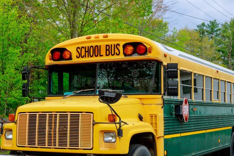 Parte dianteira do transporte educacional das crianças amarelas do ônibus escolar com sinais no estacionamento imagem de stock royalty free