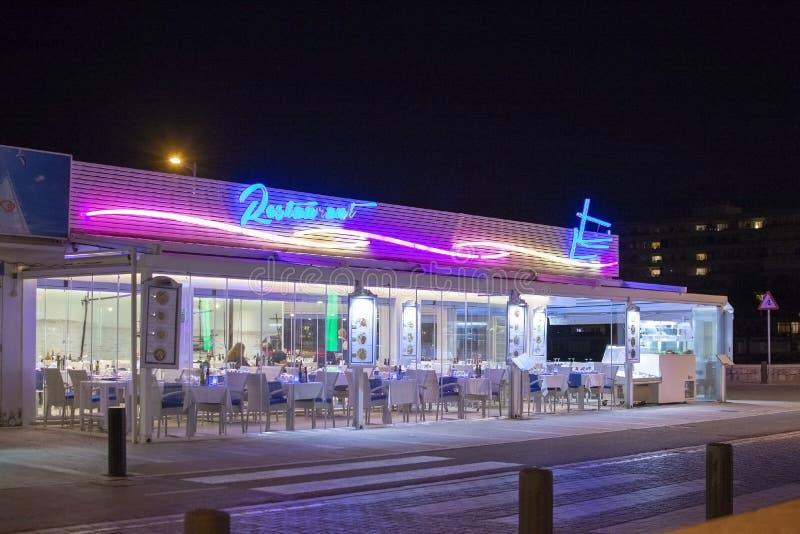 Parte dianteira iluminada de néon do restaurante dos peixes de Marisqueria em Cala Estancia na noite foto de stock royalty free