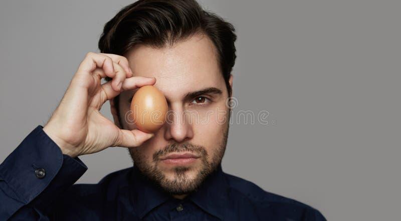 Parte dianteira orgânica fresca do ovo da galinha segura da terra arrendada do homem da CARA NO FUNDO CINZENTO Fim acima imagens de stock