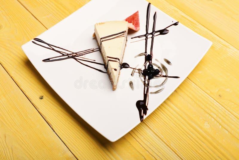 Parte do bolo de queijo no fundo de madeira amarelo Bolo servido no restaurante imagem de stock royalty free