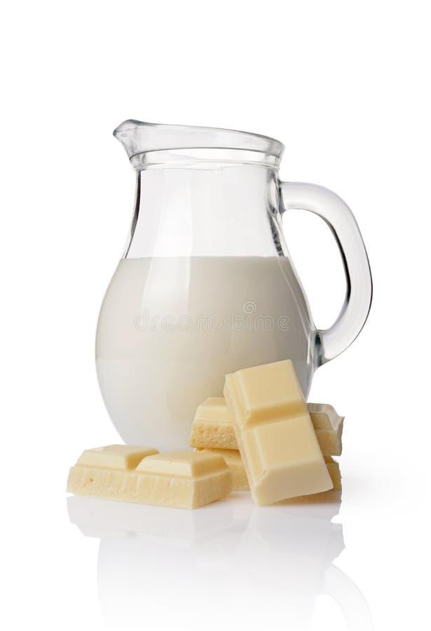 Parte do close-up da barra de chocolate branca com o jarro de vidro de leite imagem de stock royalty free