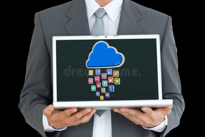 Parte do homem de negócios que guarda um portátil com ícones na tela imagem de stock